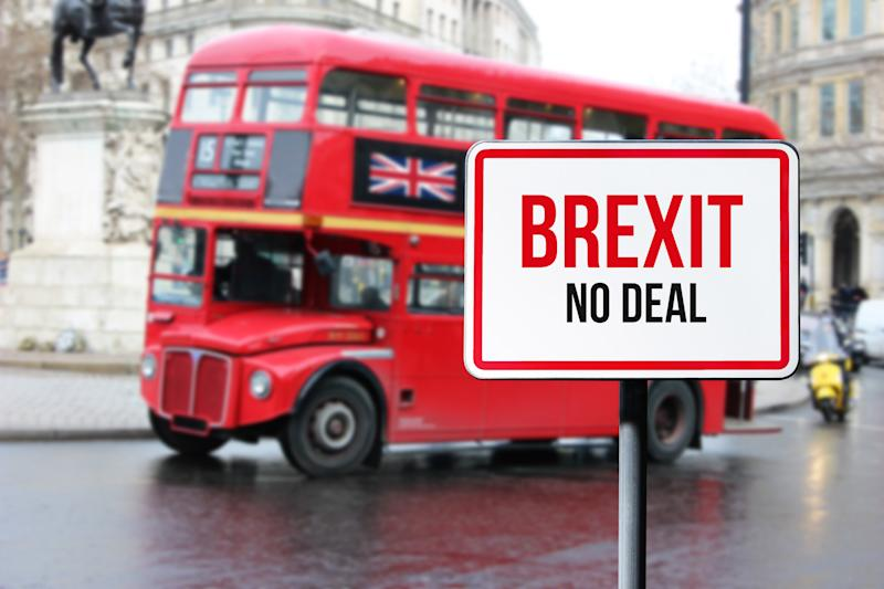 Blurred London street view with red double decker bus and Brexit no deal sign in rainy day. Possible exit of Great Britain from the EU, brexit concept.