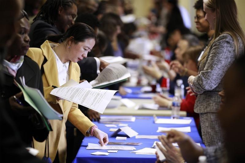 Jobseekers hold their resumes while they wait to speak with potential employers during the Dr. Martin Luther King Jr. career fair held by the New York State department of Labor in New York