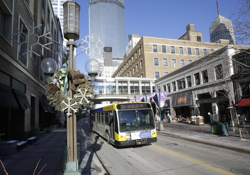 In this Tuesday, Feb. 12, 2013 photo, a bus moves past Minneapolis' bustling downtown Nicollet Mall. The Twin Cities' array of theaters and first-class museums, the state's expansive parkland and its 19 Fortune 500 company headquarters _ the second-most per capita in the country _are frequently touted selling points in attracting talented people. Gov. Mark Dayton's proposed tax increases would primarily hit company ledgers _ just as many other governors, Republicans and even some Democrats, are trying to cut their income taxes and make other changes to attract businesses. (AP Photo/Jim Mone)