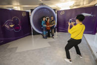 A woman poses for photos with flight attendants in a flight-themed restaurant at the Thai Airways head office in Bangkok, Thailand on Oct. 3, 2020. The airline is selling time on its flight simulators to wannabe pilots while its catering division is serving meals in a flight-themed restaurant complete with airline seats and attentive cabin crew. The airline is trying to boost staff morale, polish its image and bring in a few pennies, even as it juggles preparing to resume international flights while devising a business reorganization plan. (AP Photo/Sakchai Lalit)
