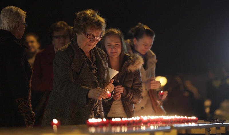 People light candles during a memorial service at the 't Stekske school in Lommel, Belgium on Thursday, March 15, 2012. A coach accident in Switzerland on Wednesday left 28 dead, including 22 children from Belgium traveling home after a skiing holiday, local police said Wednesday. Police said 24 children were injured when their Belgian bus crashed into the wall of a motorway tunnel near Sierre, south of Bern, late Tuesday. The cause of the crash on the straight stretch of road was not immediately clear. (AP Photo/Virginia Mayo)