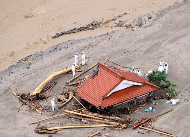 <p>In this aerial image, police officers surround a house buried by a mudslide after the torrential rain on July 6, 2017 in Asakura, Fukuoka, Japan. (Photo: The Asahi Shimbun via Getty Images) </p>