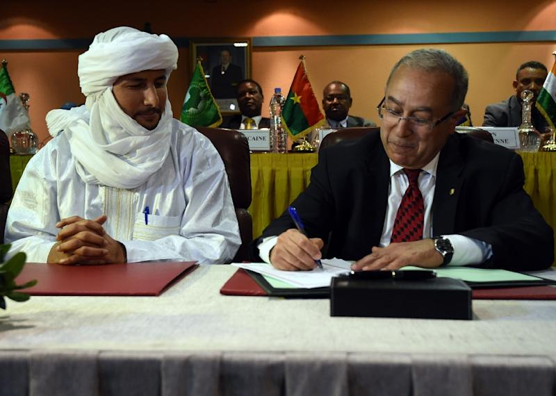 Algerian FM Ramtane Lamamra (R) signs documents overseeing a peace agreement between the Malian government and armed groups, February 19, 2015 in Algiers (AFP Photo/Farouk Batiche)