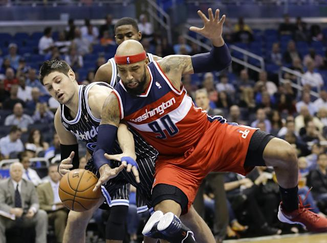 Orlando Magic's Nikola Vucevic, left, and Washington Wizards' Drew Gooden (90) go after a loose ball during the first half of an NBA basketball game in Orlando, Fla., Friday, March 14, 2014. (AP Photo/John Raoux)