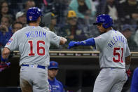 Chicago Cubs' Patrick Wisdom (16) reacts with teammate Sergio Alcantara after scoring off a sacrifice fly by Alcantara during the fourth inning of a baseball game against the San Diego Padres, Monday, June 7, 2021, in San Diego. (AP Photo/Gregory Bull)