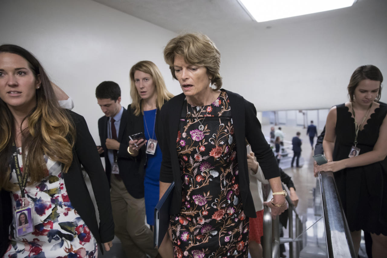 In this Sept. 19, 2017, photo, Sen. Lisa Murkowski, R-Alaska, speaks with a reporter as she arrives for a vote at the Capitol in Washington. Provisions shoehorned into the Republican health care bill dangle extra money for Alaska and Wisconsin, home states of one GOP senator whose vote party leaders desperately need and another who co-sponsored the legislation, according to analysts who've studied the legislation. (AP Photo/J. Scott Applewhite)