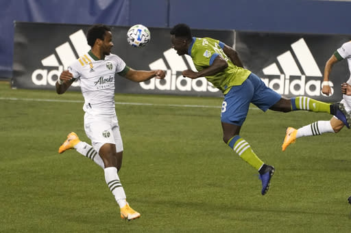 Seattle Sounders defender Kelvin Leerdam, center, heads the ball in front of Portland Timbers forward Jeremy Ebobisse, left, during the second half of an MLS soccer match, Sunday, Sept. 6, 2020, in Seattle. (AP Photo/Ted S. Warren)