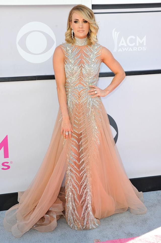 <p>The country superstar stunned in a nude, sleeveless and very glitzy number by LaBourjoisie. (Photo: Getty Images) </p>