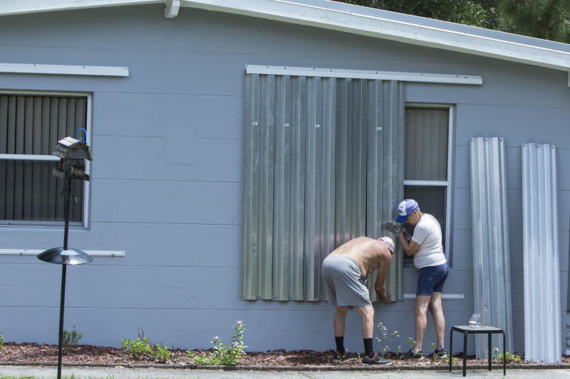 James Wolfe, 72, left, and Elaine Wolfe, 65, install shutters on their home in Vero Beach, Fla, Aug. 29, 2019. (Photo: Ellis Rua/AP)