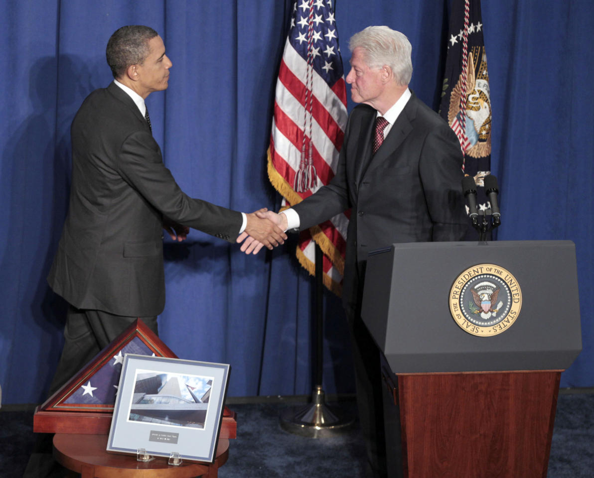 President Barack Obama, left, shakes hands with former President Bill Clinton, right, at the dedication of the Ronald H. Brown United States Mission to the United Nations Building in New York Tuesday, March 29, 2011.
