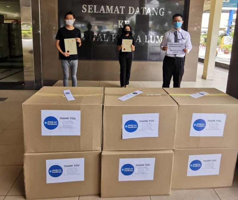 Au Jun Wei (left) and Karishma Menon (centre) handing over free face shields to a representative from Hospital Kuala Lumpur last year. Together with Leong Himn Yau, they are the founders of Feed Selangor.