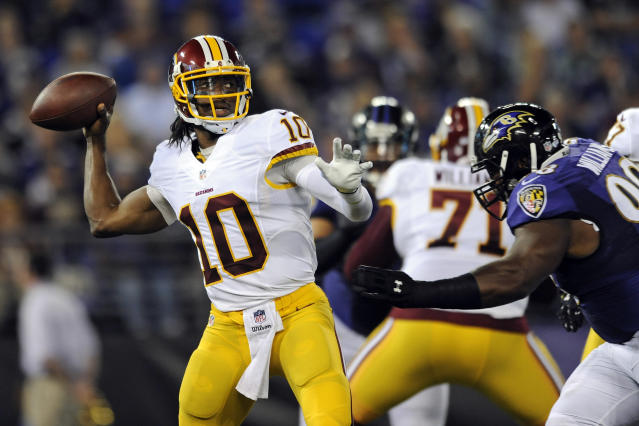 Washington Redskins quarterback Robert Griffin III, (10) throws to a receiver as he is pressured by Baltimore Ravens defensive tackle Brandon Williams in the first half of an NFL preseason football game, Saturday, Aug. 23, 2014, in Baltimore. (AP Photo/Gail Burton)