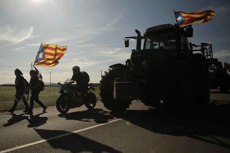 Demonstrators march along a highway near Girona, Spain, Wednesday, Oct. 16, 2019. Thousands of people have joined five large protest marches across Catalonia that are set to converge on Barcelona, as the restive region reels from two straight days of violent clashes between police and protesters. The marches set off from several Catalan towns and aimed to reach the Catalan capital by Friday. (AP Photo/Joan Mateu)