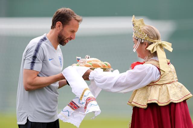 Gareth Southgate is presented with a traditional Russian karavai, a loaf of bread representing hospitality, before training got underway. (Getty)