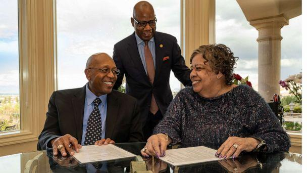PHOTO: Calvin Tyler Jr. and his wife, Tina, smile at each other after signing a giving pledge for $20 million to Morgan State University as the university's president, David K. Wilson, looks on at the Tylers' home in Las Vegas on Feb. 20, 2021.  (Paul