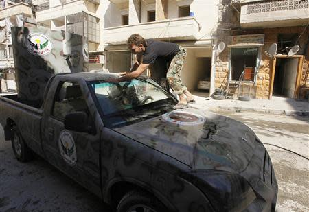 "A member of ""Free Men of Syria"" (Ahrar Suriya) brigade, operating under the Free Syrian Army, washes a vehicle used by Free Syrian Army fighters in Aleppo's Bustan al-Qasr, September 9, 2013. REUTERS/Hamid Khatib"