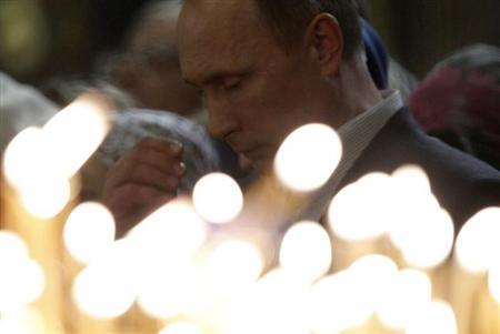 Russia's President Putin gestures as he attends the Orthodox Christmas service at the Holy Face of Christ the Savior Church in the Russian southern city of Sochi