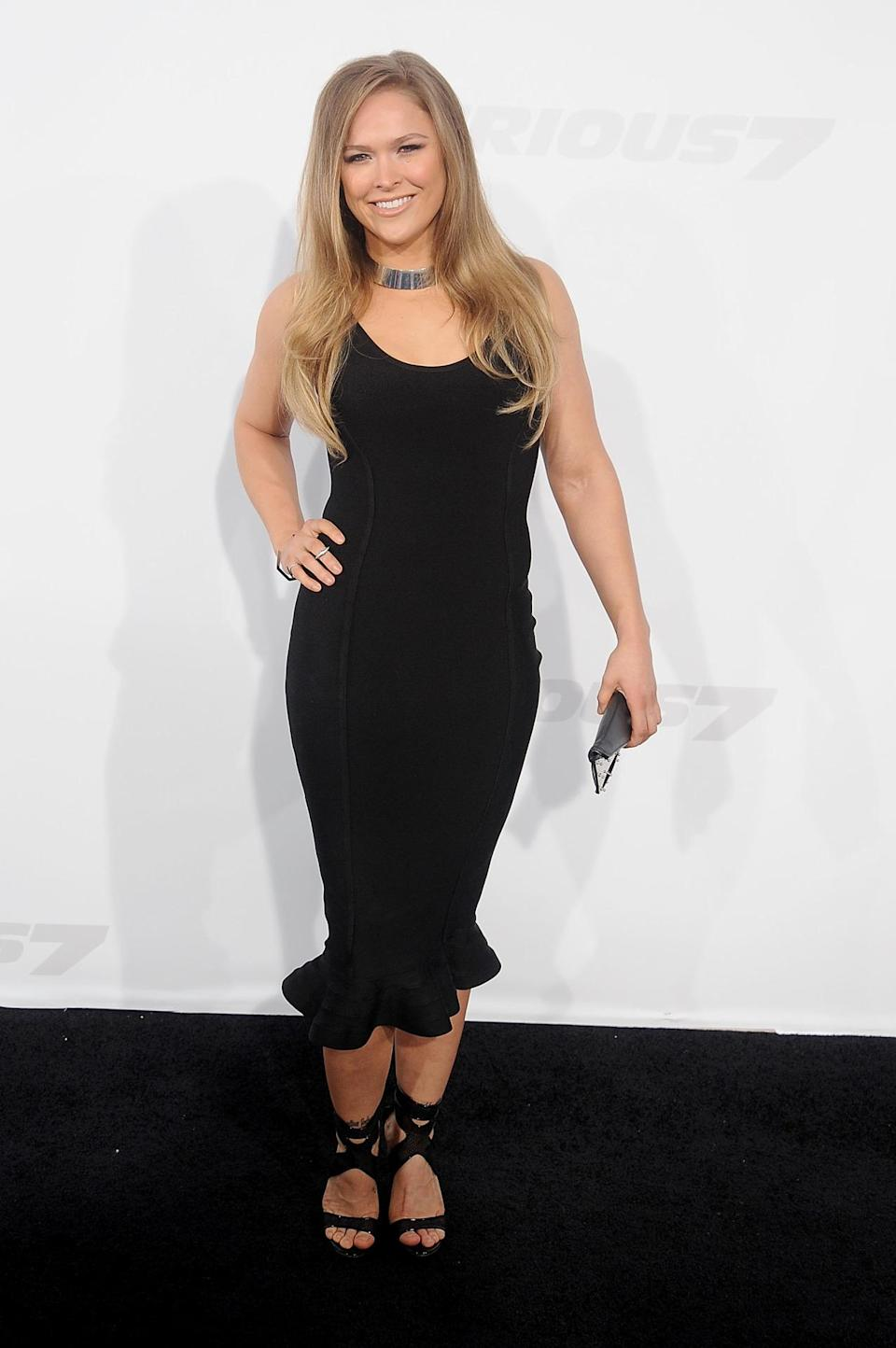 """The UFC champion is rarely seen out of fighting form, but at the """"Furious 7"""" premiere she showed off her fashion chops in a form-fitting mid-length black dress accompanied with a very '90s silver metal choker (very appropriate for a choke holder, no?)."""