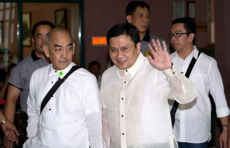 Jose 'Jinggoy' Estrada  waves as he arrives at the graft court for his arraignment in Manila