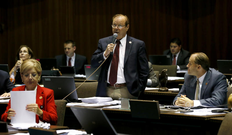 Rep. Frank Pratt, R-Casa Grande, middle, speaks as Rep. Ethan Orr, R-Tucson, right, listens while Rep. Karen Fann, R-Prescott, adjusts amendment paperwork in a special session budget battle for Medicaid funding on Wednesday, June 12, 2013, in Phoenix. The Arizona Legislature is on track to pull an all-nighter and work into Thursday to finish a state budget and approve Medicaid expansion. (AP Photo/Ross D. Franklin)
