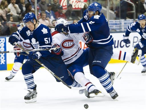 Toronto Maple Leafs defenseman Jake Gardiner, left, and Luke Schenn, right, take out Montreal Canadiens forward Erike Cole, center, during the third period of an NHL hockey game, Saturday, Feb. 11, 2012, in Toronto. The Canadiens won 5-0. (AP Photo/The Canadian Press, Nathan Denette)