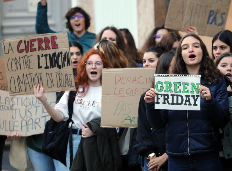 """Young people protests against Black Friday, Nov 29, 2019, in Bayonne, southwestern France. Placard at left reads """"The war against climate inaction is engaged"""". Some French lawmakers want to ban the Black Friday sales, the post-Thanksgiving sales event that has morphed into a global phenomenon. (AP Photo/Bob Edme)"""
