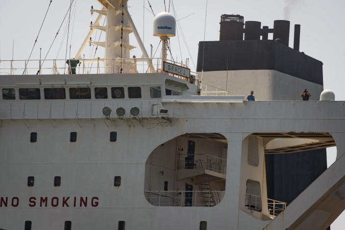 Crew members stand on the Grace 1 supertanker in the British territory of Gibraltar, Thursday, Aug. 15, 2019, seized last month in a British Royal Navy operation off Gibraltar. The United States moved on Thursday to halt the release of the Iranian supertanker Grace 1, detained in Gibraltar for breaching EU sanctions on oil shipments to Syria, thwarting efforts by authorities in London and the British overseas territory to defuse tensions with Tehran.(AP Photo/Marcos Moreno)