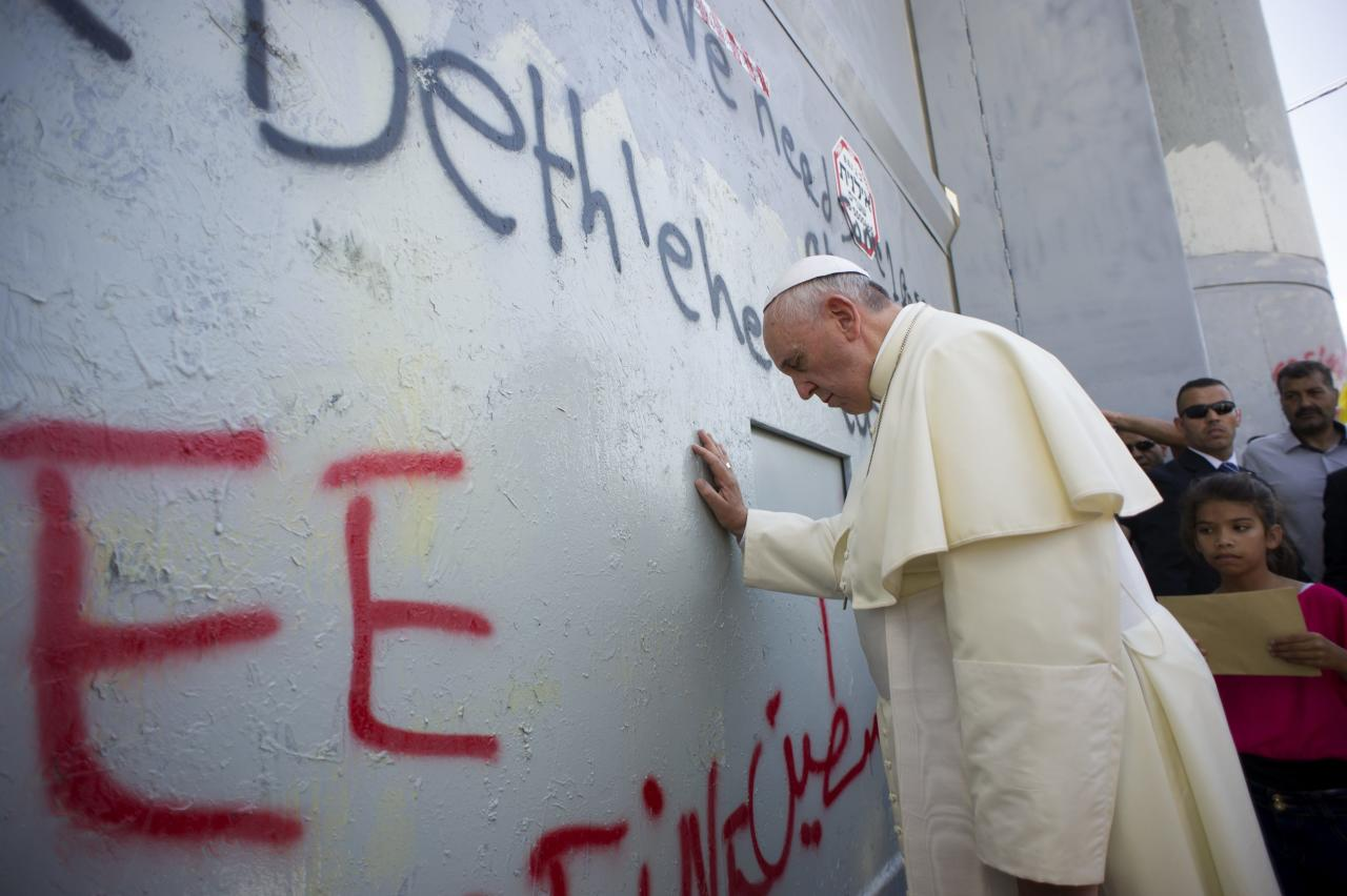 Pope Francis touches the wall that divides Israel from the West Bank, on his way to celebrate a mass in Manger Square next to the Church of the Nativity in the West Bank city of Bethlehem May 25, 2014. Pope Francis made an impassioned plea for peace on a pilgrimage on Sunday to Bethlehem, the traditional birthplace of Jesus, urging an intensified effort to end the Israeli-Palestinian conflict. REUTERS/Osservatore Romano (WEST BANK - Tags: RELIGION POLITICS TPX IMAGES OF THE DAY) ATTENTION EDITORS - NO SALES. NO ARCHIVES. FOR EDITORIAL USE ONLY. NOT FOR SALE FOR MARKETING OR ADVERTISING CAMPAIGNS. THIS IMAGE HAS BEEN SUPPLIED BY A THIRD PARTY. IT IS DISTRIBUTED, EXACTLY AS RECEIVED BY REUTERS, AS A SERVICE TO CLIENTS. NO COMMERCIAL USE