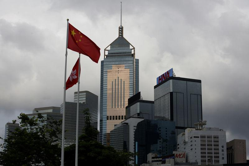A Chinese national flag flies in front of commercial buildings in Hong Kong