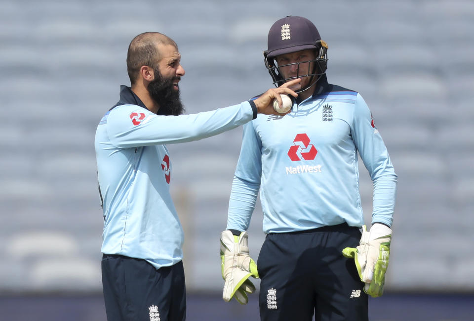 England's Moeen Ali, left, interacts with captain Jos Buttler before bowling his next delivery during the second One Day International cricket match between India and England at Maharashtra Cricket Association Stadium in Pune, India, Friday, March 26, 2021. (AP Photo/Rafiq Maqbool)