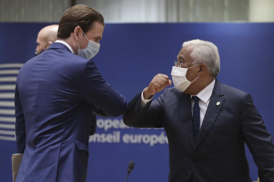 Austria's Chancellor Sebastian Kurz, left, greets Portugal's Prime Minister Antonio Costa, right, with an elbow bump during a round table meeting at an EU summit in Brussels, Friday, July 17, 2020. Leaders from 27 European Union nations meet face-to-face on Friday for the first time since February, despite the dangers of the coronavirus pandemic, to assess an overall budget and recovery package spread over seven years estimated at some 1.75 trillion to 1.85 trillion euros. (Stephanie Lecocq, Pool Photo via AP)