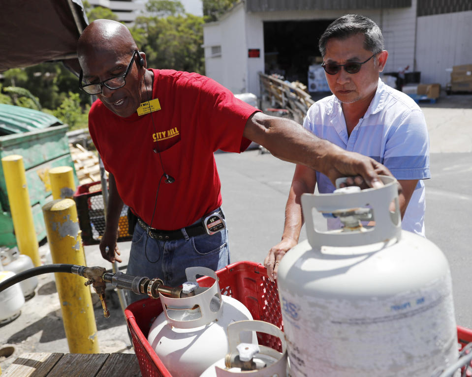 <p>City Mill hardware store sales associate Thom West, left, fills up several propane tanks for Tony Cao, Wednesday, Aug. 22, 2018, in Honolulu. Cao said he waited nearly two hours in line for propane. Although he already stocked up on fresh food, Cao the most important things to have during Hurricane Lane were Spam and Vienna savage as you don't need to cook them. (Photo: Marco Garcia/AP) </p>
