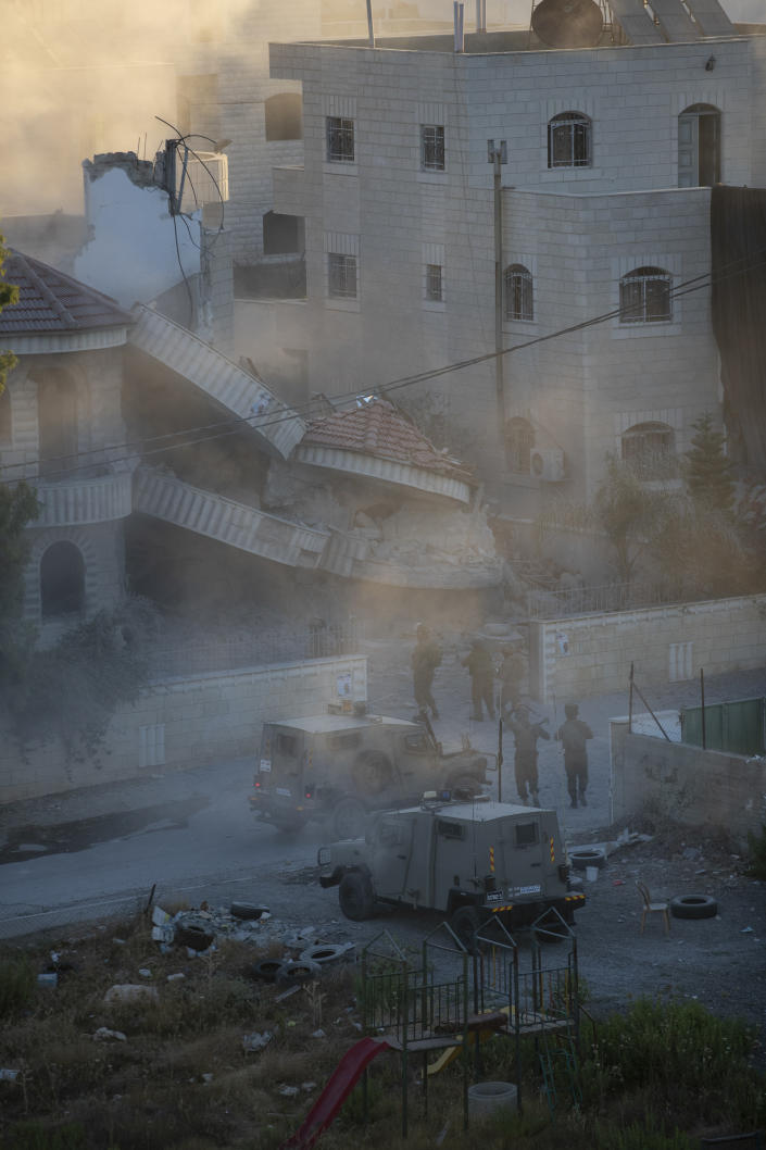 An Israeli army unit inspects the house of the Palestinian American Muntasser Shalaby following a controlled explosion demolition in the West Bank village of Turmus Ayya, north of Ramallah, Thursday, July 8, 2021. Israeli forces on Thursday demolished the Shalaby family home after being accused of being involved in a deadly attack on Israelis in the West Bank in May. (AP Photo/Nasser Nasser)