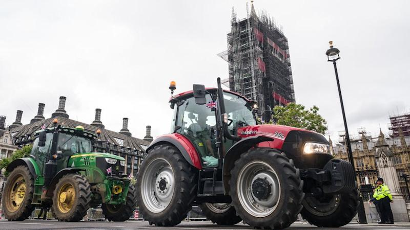 Farmers drive their tractors past the Houses of Parliament, watched by policemen