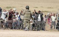 A Turkish soldier stands guard as Syrian Kurds wait behind the border fence to cross into Turkey near the southeastern town of Suruc in Sanliurfa province, September 19, 2014. REUTERS/Stringer