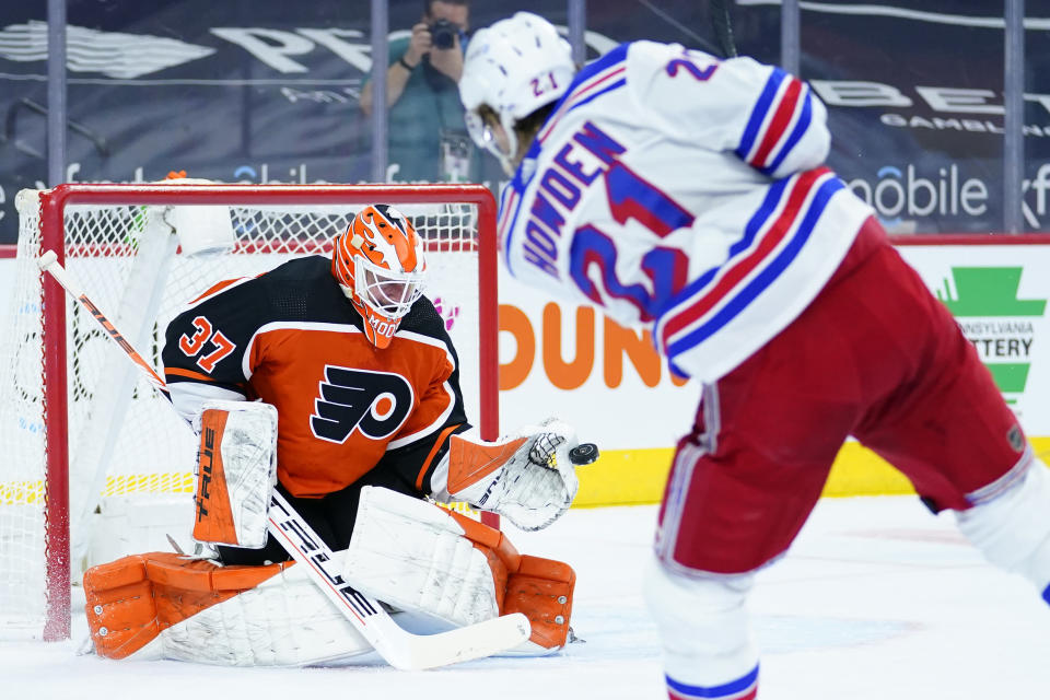 Philadelphia Flyers' Brian Elliott, left, blocks a shot by New York Rangers' Brett Howden during the second period of an NHL hockey game, Wednesday, Feb. 24, 2021, in Philadelphia. (AP Photo/Matt Slocum)