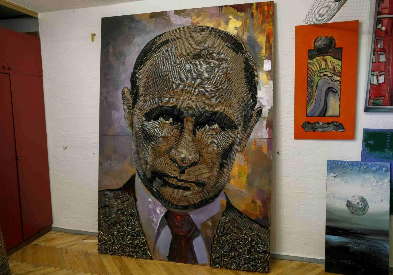 "A portrait of Russian President Vladimir Putin, made out of 5,000 cartridges brought from the frontline in eastern Ukraine, named ""The Face of War"" is seen in the studio of Ukrainian artist Dariya Marchenko, in Kiev, July 23, 2015.  The portrait will be presented along with a novel which will tell personal stories of six people involved in this project including Daria's own story and stories of people who helped her to collect shells from the frontline. Daria Marchenko calls her art approach philosophic symbolism where every element has its hidden meaning. In her works cartridges mean human's life that was brutally ended. Picture taken July 23, 2015. REUTERS/Gleb Garanich"