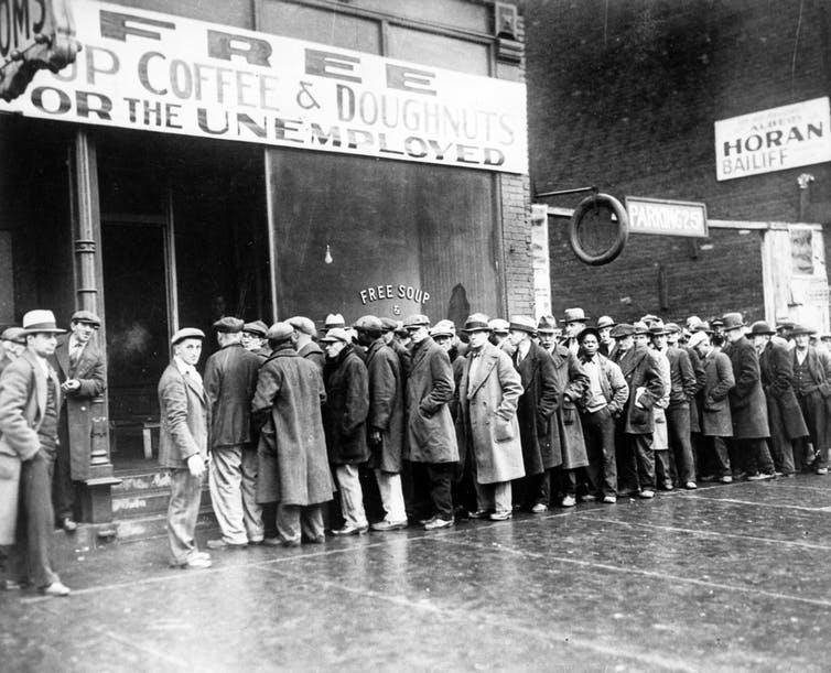 Black and white photo of men in coats and hats queing outside building with sign reading 'Free soup coffee and doughnuts for the unemployed'.