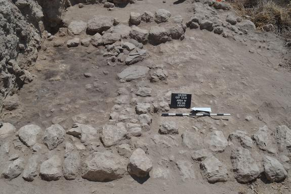Burned ruins and fired mudbrick collapse, as well as smashed pottery, reveal the late Bronze Age destruction at the city. On the left is the room where several pottery vessels, a scarab of Amenhotep III, a cache of cylinder seals, as well as s