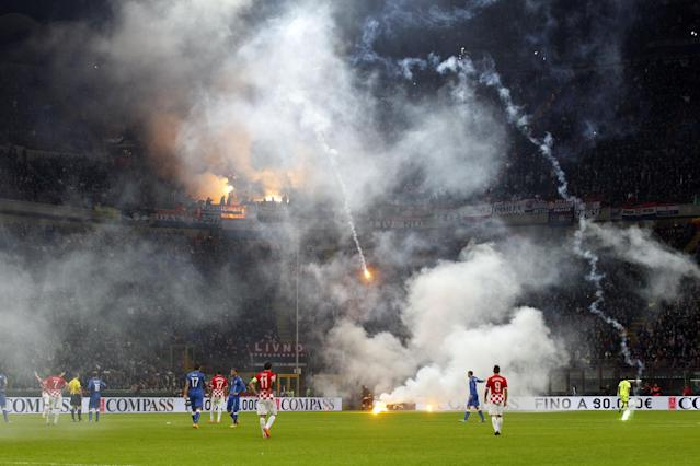 Flares are launched by Croatia supporters during the Euro 2016 qualifying soccer match between Italy and Croatia, at the San Siro stadium in Milan, Italy, Sunday, Nov. 16, 2014. The match was temporarily suspended following the launch of flares and clashes with Italian riot police on the stands. (AP Photo/Luca Bruno)