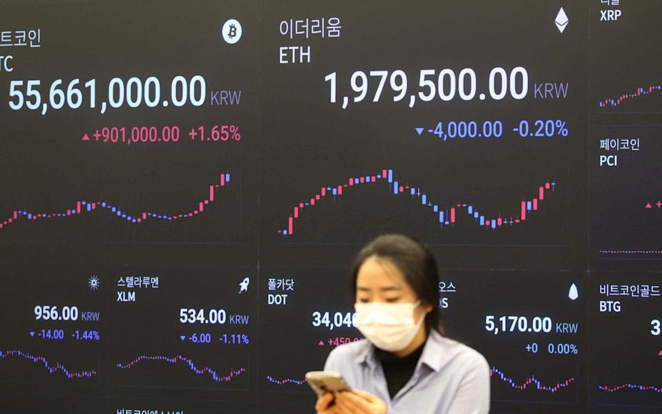 A woman looks at a mobile phone in front of an electronic signboard of cryptocurrency exchange in Seoul, South Korea, 17 February 2021 - KIM CHUL-SOO/Shutterstock