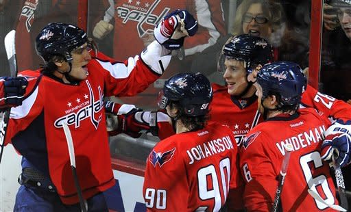 Washington Capitals' Alex Ovechkin, left, of Russia, Marcus Johansson (90), of Sweden, Dennis Wideman (6) and Alexander Semin(28), of Russia, celebrate Semins' goal in the second period of their NHL hockey game against the Carolina Hurricanes, Sunday, Jan. 15, 2012, in Washington. The Capitals defeated the Hurricanes 2-1. (AP Photo/Richard Lipski)