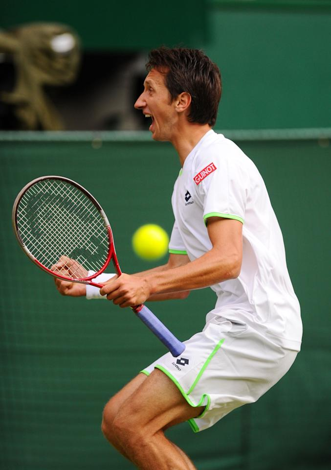 LONDON, ENGLAND - JUNE 26: Sergiy Stakhovsky of Ukraine celebrates match point during his Gentlemen's Singles second round match against Roger Federer of Switzerland on day three of the Wimbledon Lawn Tennis Championships at the All England Lawn Tennis and Croquet Club on June 26, 2013 in London, England. (Photo by Mike Hewitt/Getty Images)
