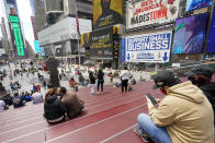 Visitors to New York's Time Square take in the view from the TKTS stairway, Tuesday, April 27, 2021, in New York. In recent weeks, tourism indicators for New York City like hotel occupancy and museum attendance that had fallen off a pandemic cliff have ticked up slightly. It's a welcome sight for a city where the industry has been decimated by the impact of the coronavirus. (AP Photo/Mary Altaffer)