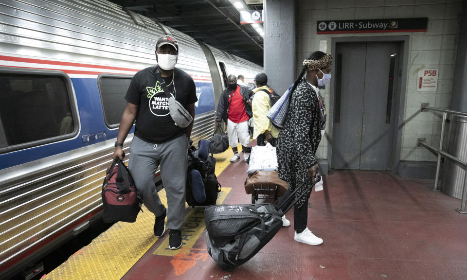 Travelers arriving on a train that originated in Miami carry their luggage at Amtrak's Penn Station, Thursday, Aug. 6, 2020, in New York. Mayor Bill de Blasio is asking travelers from 34 states, including Florida where COVID-19 infection rates are high, to quarantine for 14 days after arriving in the city. (AP Photo/Mark Lennihan)