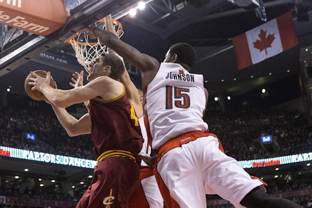 Cleveland Cavaliers' Tyler Zeller, left, shoots as Toronto Raptors' Amir Johnson defends during the first half of an NBA basketball game in Toronto, Friday, Feb. 21, 2014. (AP Photo/The Canadian Press, Chris Young)