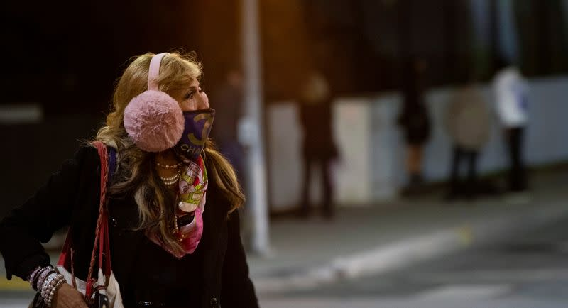 A woman wearing a protective face mask and earmuffs crosses the street in Beverly Hills