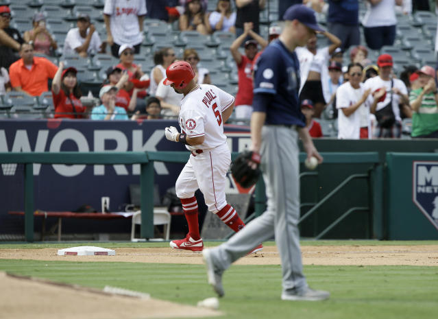 Los Angeles Angels designated hitter Albert Pujols, left, rounds third after hitting a three-run home run with Tampa Bay Rays starting pitcher Ryan Yarbrough, right, looking away during the fifth inning of a baseball game in Anaheim, Calif., Sunday, Sept. 15, 2019. (AP Photo/Alex Gallardo)