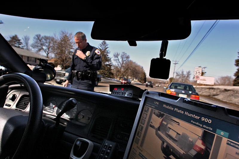 FILE - In this March 18, 2011, file photo, Maplewood, Minn., police officer Steven Hiebert, standing, uses the License Plate Ready System, which consists of a camera that photographs license plates and then compares them with those in a database of stolen vehicles. Oregon privacy advocates, argue that police shouldn't be able to track people's movements, particularly without suspicion of criminal activity. (AP Photo/Star Tribune, Jim Gehrz, File)
