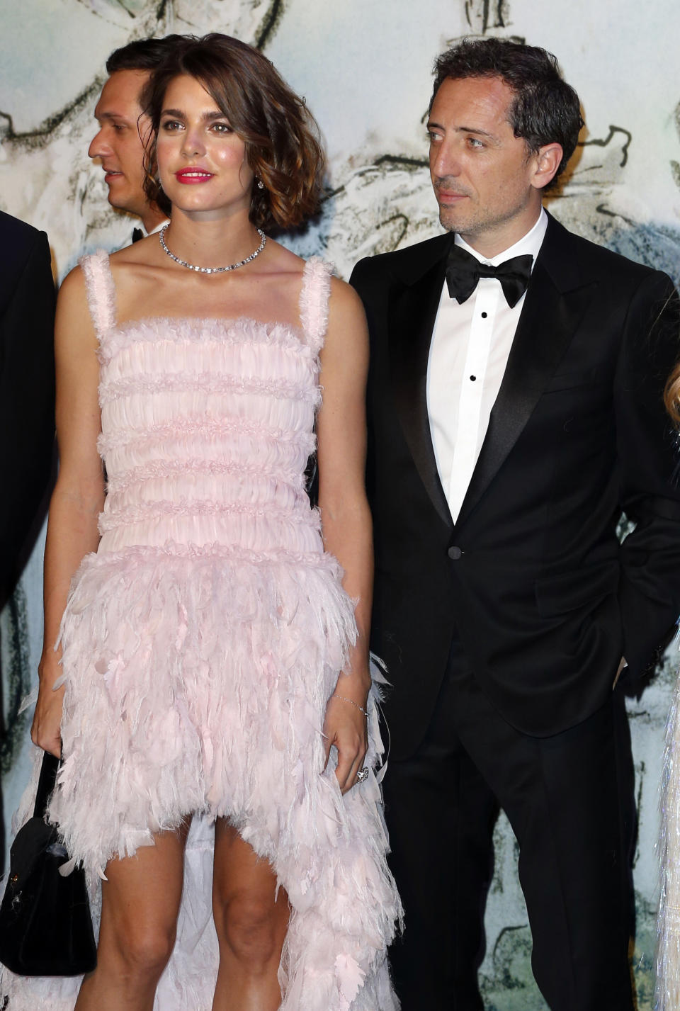 """Charlotte Casiraghi and French humorist Gad Elmaleh poses prior to the annual Rose Ball at the Monte-Carlo Sporting Club in Monaco, on March 23, 2013. The Rose Ball is one of the major charity events in Monaco. Created in 1954, it benefits the Princess Grace Foundation. Directed by German Couturier Karl Lagerfeld, this year's event named """"La Belle Epoque"""" (Beautiful Era), was celebrated in honor of the Societe des bains de mer (SBM),  a prominent player in Monaco's tourism industry. AFP PHOTO /POOL/ VALERY HACHE        (Photo credit should read VALERY HACHE/AFP via Getty Images)"""